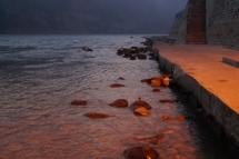 Where footpath lights collide with daybreak in Rishikesh walking path along River Ganga